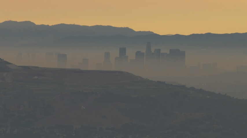 HD stock footage aerial video of a smoggy skyline beyond hills, Downtown Los Angeles, California, sunset Aerial Stock Footage | CBAX01_067