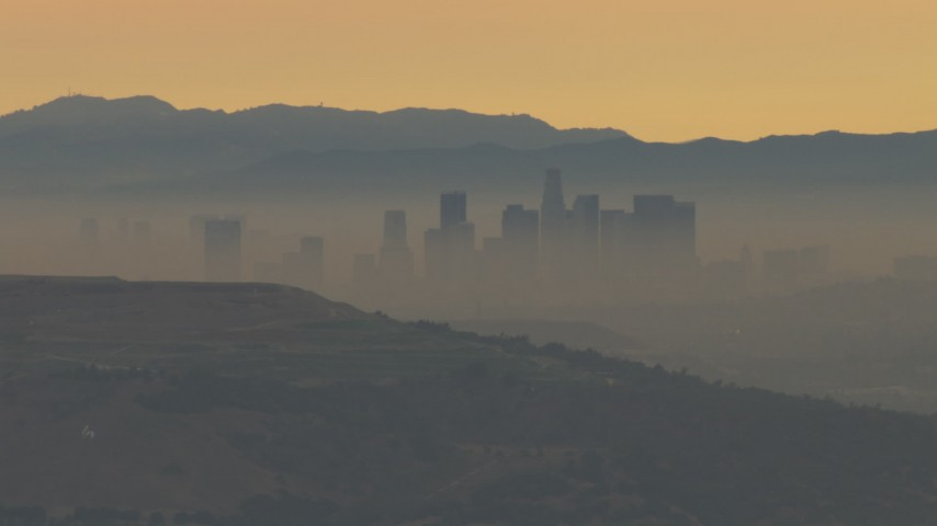 HD stock footage aerial video of smoggy skyline beyond hills, Downtown Los Angeles, California, sunset Aerial Stock Footage | CBAX01_068