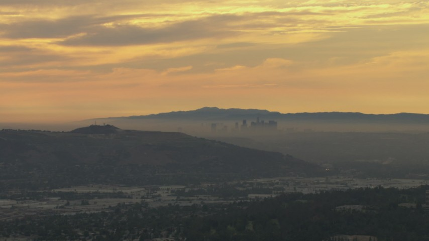HD stock footage aerial video of smoggy skyline beyond hills, Downtown Los Angeles, California, sunset Aerial Stock Footage | CBAX01_069