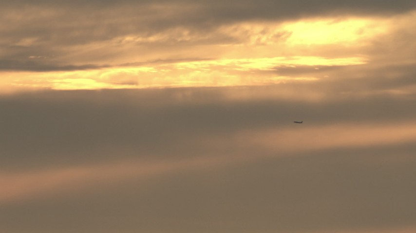 HD stock footage aerial video of sunset-lit clouds, revealing a passenger jet flying by, sunset, Southern California Aerial Stock Footage | CBAX01_071