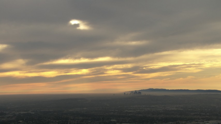 HD aerial stock footage video of the distant skyline, clouds, Downtown Los Angeles, California, sunset Aerial Stock Footage | CBAX01_077