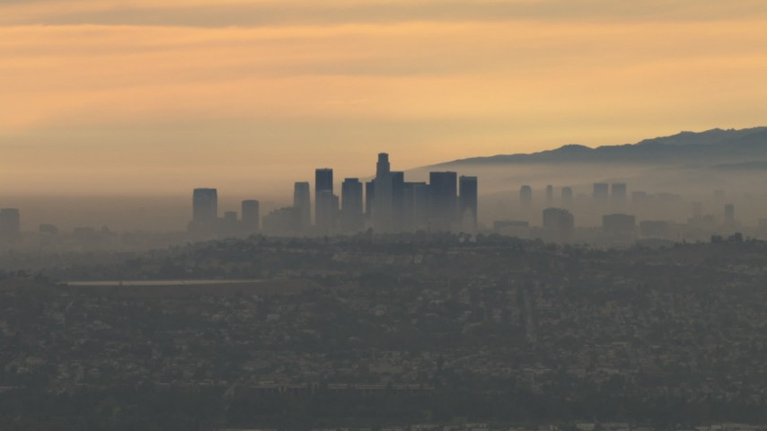 HD stock footage aerial video of flying by smoggy skyline, cloudy, Downtown Los Angeles, California, sunset Aerial Stock Footage | CBAX01_080