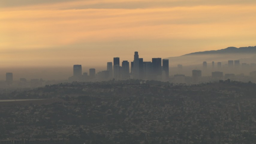 HD stock footage aerial video of passing the smoggy skyline, cloudy, Downtown Los Angeles, California, sunset Aerial Stock Footage | CBAX01_082