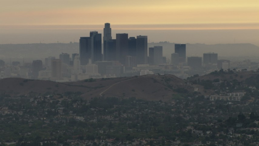 HD stock footage aerial video of a smoggy skyline, hillside neighborhood, Downtown Los Angeles, California, sunset Aerial Stock Footage | CBAX01_095