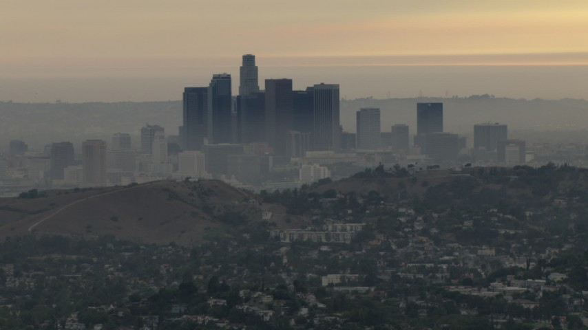 HD stock footage aerial video of the smoggy skyline, hillside neighborhood, Downtown Los Angeles, California, sunset Aerial Stock Footage | CBAX01_096