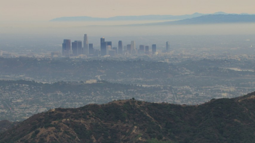 HD stock footage aerial video of flying over Verdugo Mountains, by hazy Downtown Los Angeles, California Aerial Stock Footage | CBAX01_117