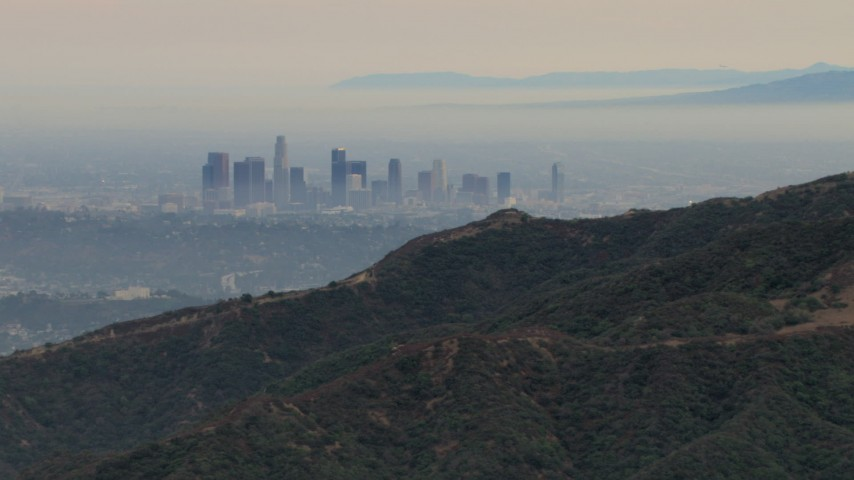 HD aerial video of flying by hazy skyline from Verdugo Mountains, Downtown Los Angeles, California Aerial Stock Footage | CBAX01_118