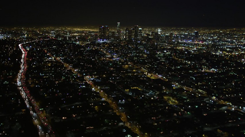 5K aerial video tilt up revealing downtown Los Angeles skyline at night, California Aerial Stock Footage DCA01_009