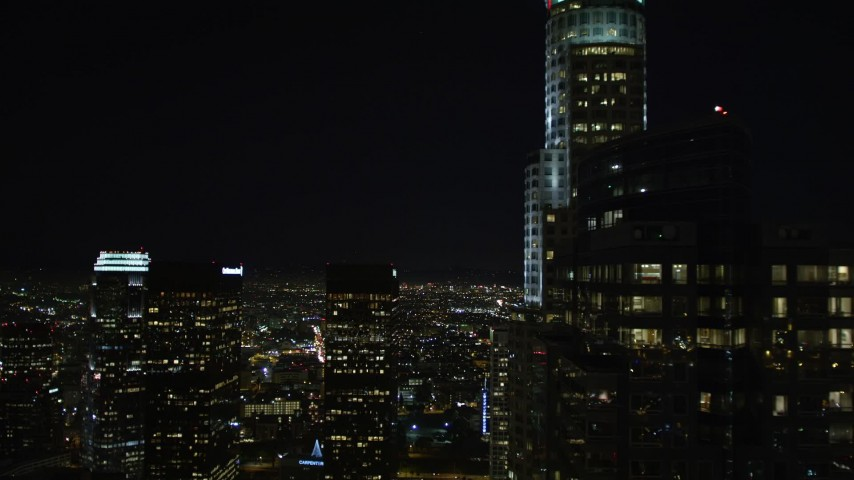5K aerial video following 5th Street, tilt up revealing skyscrapers and city lights in Downtown Los Angeles at night, California Aerial Stock Footage | DCA01_017