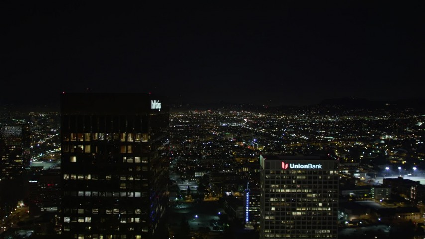 5K aerial video flying between Paul Hastings Tower and Union Bank Plaza toward Hollywood city lights at night, Los Angeles, California Aerial Stock Footage | DCA01_018