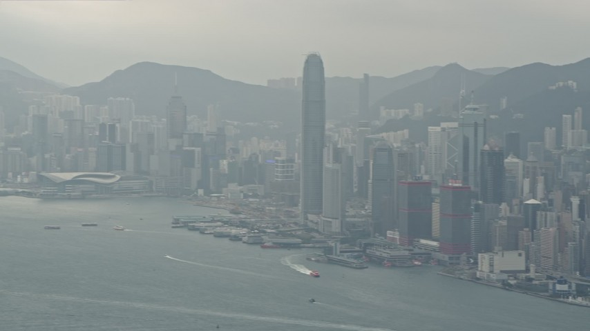 4K stock footage aerial video tilt from a ferry and pan across Hong Kong Island and Victoria Harbor to reveal Kowloon, China Aerial Stock Footage | DCA02_015