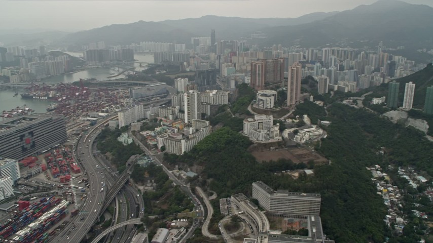 4K stock footage aerial video pan from Port of Hong Kong and office buildings to reveal Kwai Chung apartment buildings, Hong Kong, China Aerial Stock Footage | DCA02_018