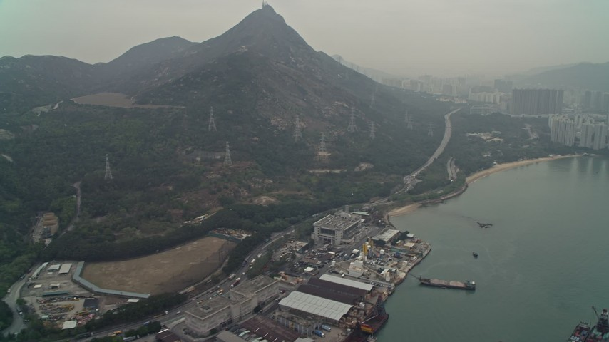 4K stock footage aerial video tilt from warehouse buildings to reveal Castle Peak and waterfront apartments, New Territories, Hong Kong, China Aerial Stock Footage | DCA02_057