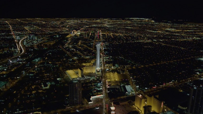4K stock footage aerial video approaching Stratosphere with city sprawl in background, Las Vegas, Nevada Night Aerial Stock Footage | DCA03_001
