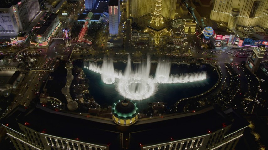 4K aerial video of flying over The Bellagio with Paris in background, tilting to the water show, Las Vegas, Nevada Night Aerial Stock Footage DCA03_023