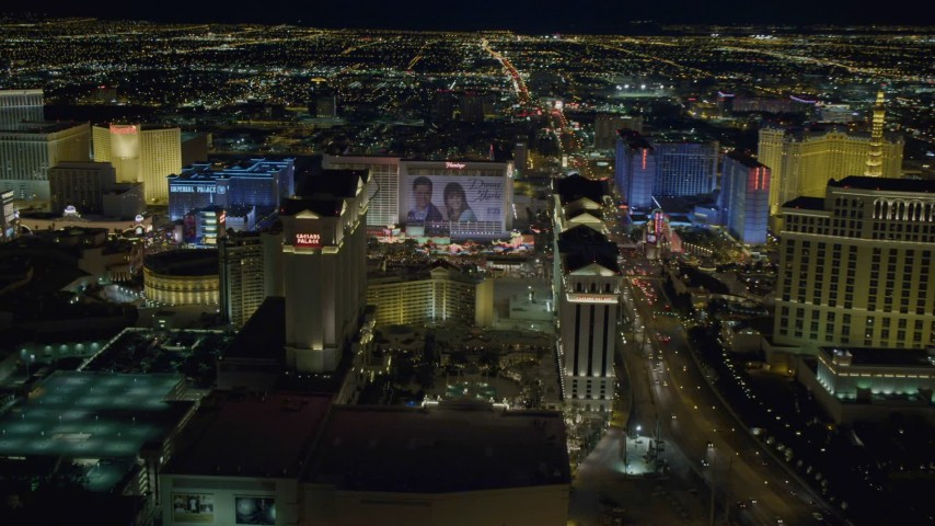 4K stock footage aerial video of panning across Las Vegas Strip, zooming in on Caesar's Palace, Nevada Night Aerial Stock Footage | DCA03_189