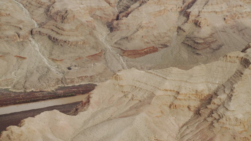 4K stock footage aerial video of panning across rock formations in Grand Canyon, revealing Colorado River, Arizona Aerial Stock Footage | DCA04_056