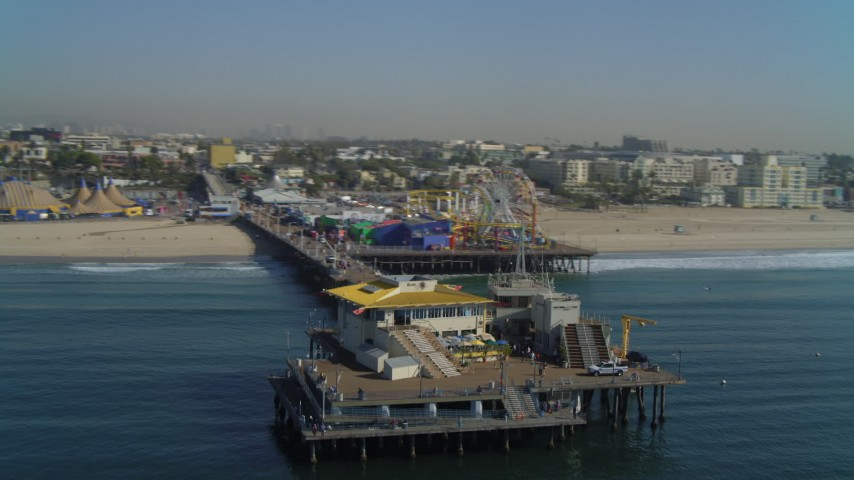 4K aerial video of fly by Santa Monica Pier, ascend and pan back to pier, Santa Monica, California Aerial Stock Footage | DCA05_080