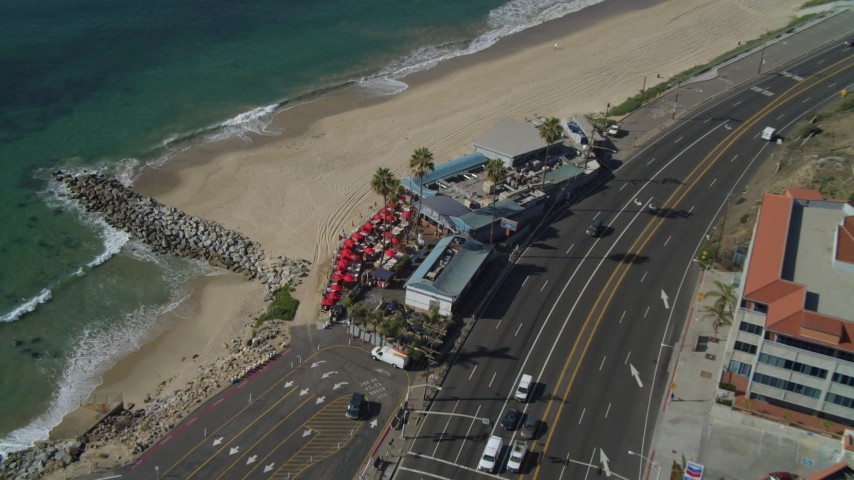 4K aerial video of Highway 1 along the coast, tilt to restaurant, Pacific Palisades, California Aerial Stock Footage | DCA05_099