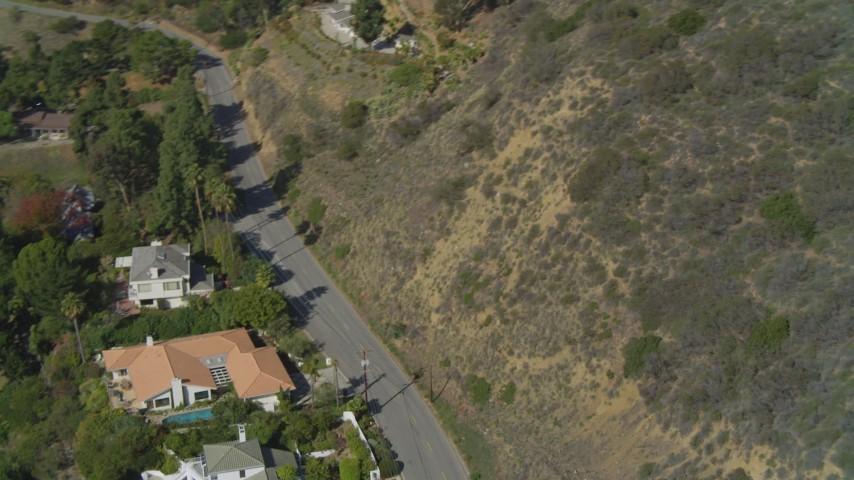Pan by hill, revealing neighborhood on cliff overlooking ocean, Malibu, California Aerial Stock Footage | DCA05_108