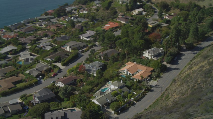 4K stock footage aerial video pan to reveal neighborhood on cliff overlooking ocean, Malibu, California Aerial Stock Footage | DCA05_108