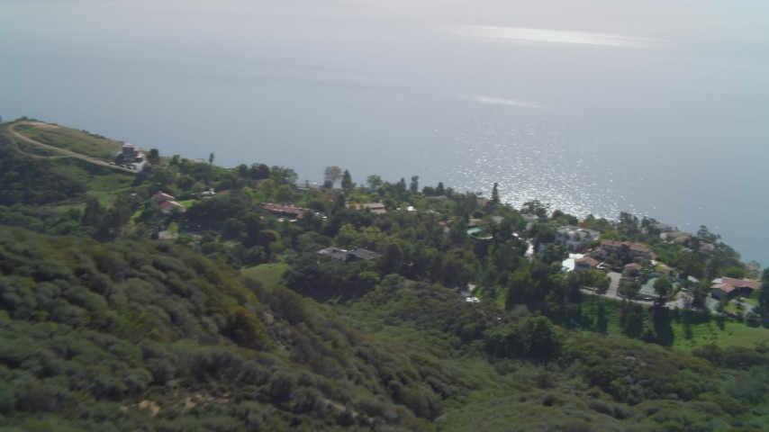 4K stock footage aerial video of hiking trail on hill, homes on cliff overlooking the Pacific Ocean, Malibu, California Aerial Stock Footage | DCA05_110
