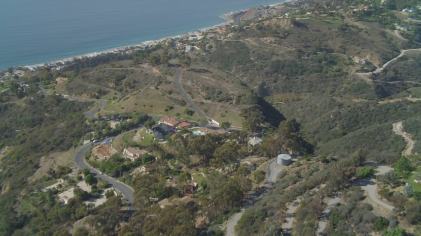 4K aerial video pan across hills, revealing residential neighborhoods, coastline, Malibu, California Aerial Stock Footage | DCA05_111