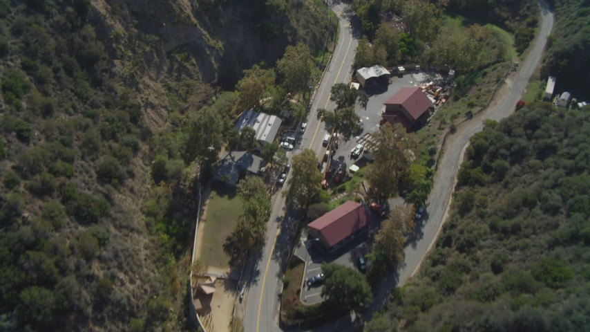 Pan across a canyon, tilt up, reveal neighborhood, coast, ocean, Malibu, California Aerial Stock Footage | DCA05_114