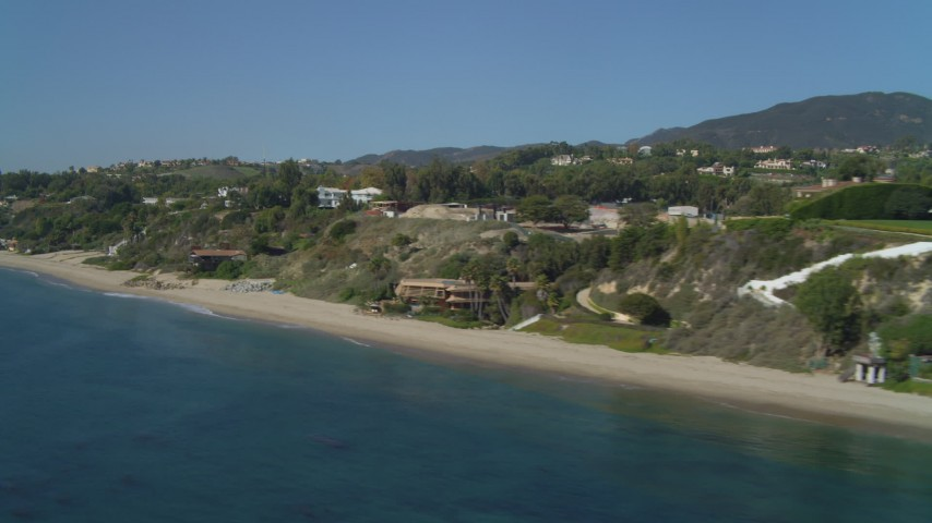 Flying over the ocean, by coastal homes, Malibu, California Aerial Stock Footage | DCA05_127