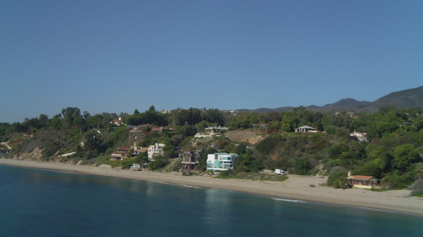 Flying over the ocean, by coastal homes, Malibu, California Aerial Stock Footage | DCA05_128