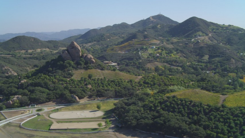Pan across vineyards, revealing hilltop rock formation, Malibu, California Aerial Stock Footage | DCA05_134