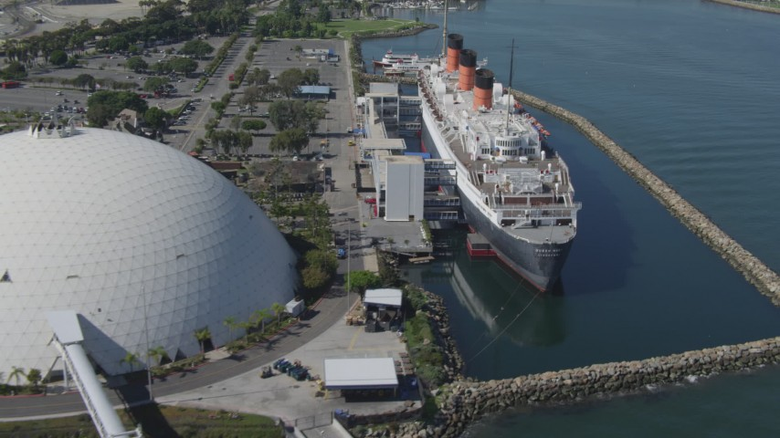 4K stock footage aerial video fly away from RMS Queen Mary, reveal Carnival Cruise Lines terminal, Long Beach, California Aerial Stock Footage | DCA06_025