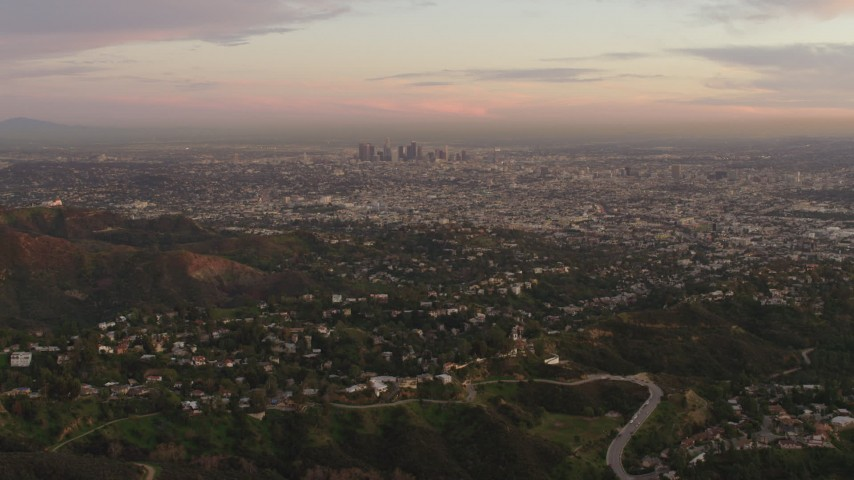 4K stock footage aerial video of flying over Hollywood Hills, revealing Downtown skyline, Los Angeles, California, sunset Aerial Stock Footage | DCA07_001