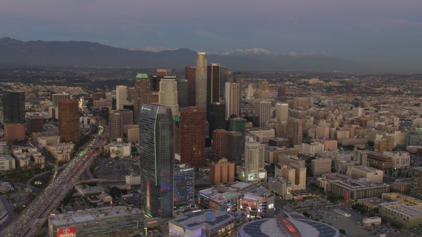 4K stock footage aerial video of flying by Downtown skyscrapers, over Highway 110, mountains in the distance, Los Angeles, California, twilight Aerial Stock Footage | DCA07_012