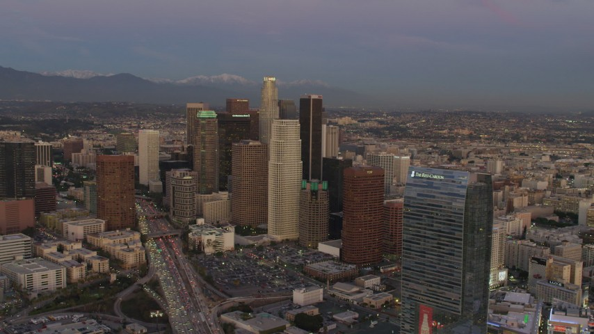 4K aerial video of flying by Downtown skyscrapers, mountains in the distance, Los Angeles, California, twilight Aerial Stock Footage | DCA07_013