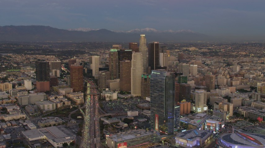4K aerial video of approaching Downtown skyscrapers, The Ritz-Carlton, mountains in the distance, Los Angeles, California, twilight Aerial Stock Footage | DCA07_016
