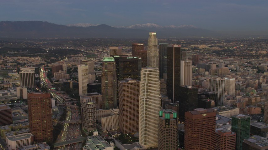 4K stock footage aerial video of approaching Downtown skyscrapers, US Bank Tower, mountains in the distance, Los Angeles, California, twilight Aerial Stock Footage | DCA07_017