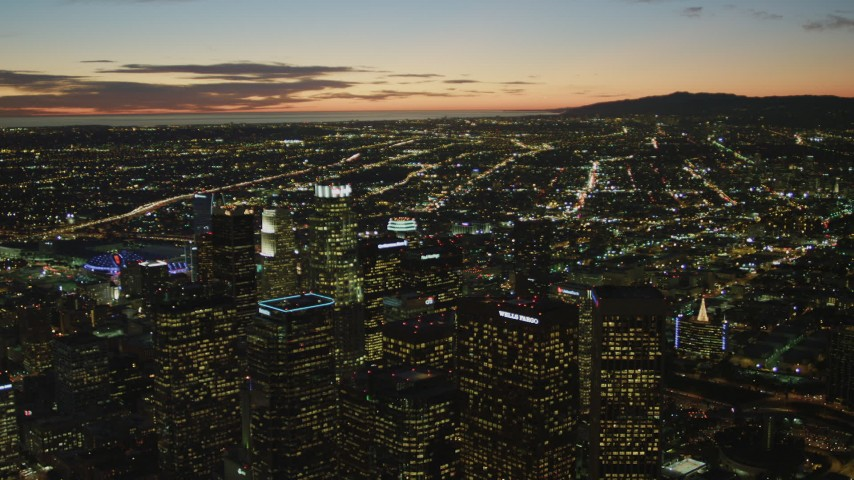 4K stock footage aerial video of flying by Downtown skyscrapers, coast and clouds in the distance, Los Angeles, California, twilight Aerial Stock Footage | DCA07_053