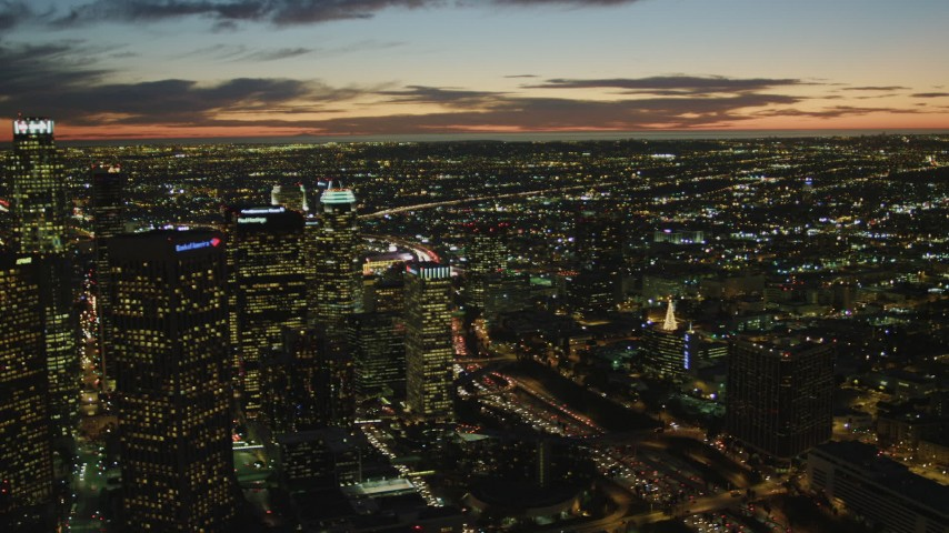 4K stock footage aerial video of flying by Downtown skyscrapers, coast and clouds in the distance, Los Angeles, California, twilight Aerial Stock Footage | DCA07_054