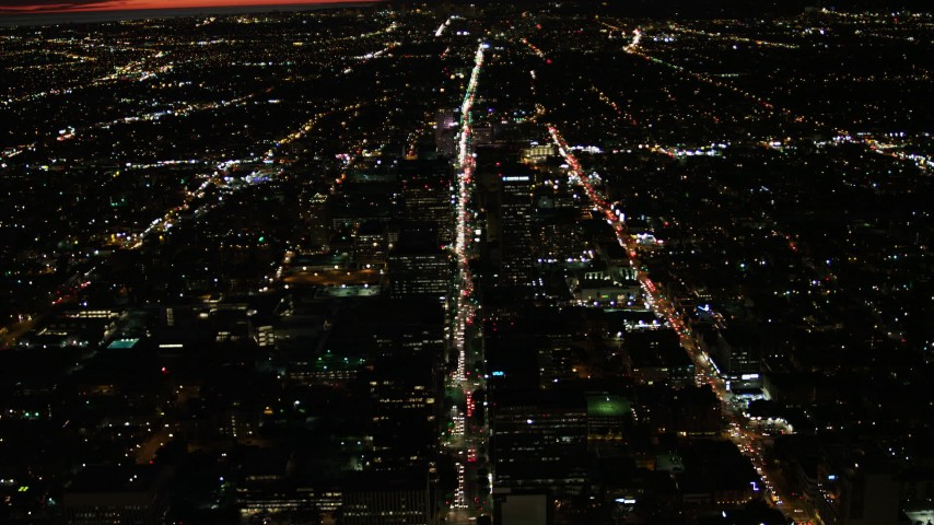 4K stock footage aerial video of following Wilshire Blvd through Koreatown and tilt to a wider view of Los Angeles, California, night Aerial Stock Footage | DCA07_066
