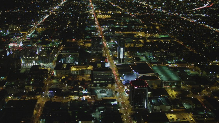 4K stock footage aerial video of following Sunset Boulevard, tilt down on Cinerama Dome, Hollywood, California, night Aerial Stock Footage | DCA07_083