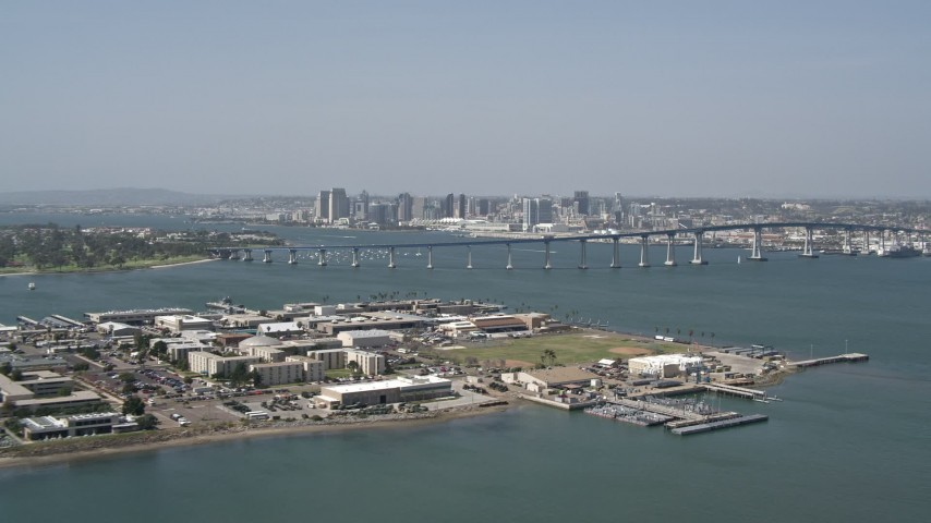 4K aerial video of a reverse view of the Coronado Bridge, city skyline, and military base, San Diego, California Aerial Stock Footage DCA08_025