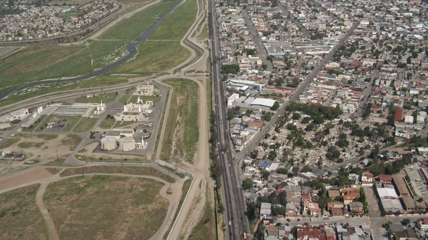 4K stock footage aerial video of following a border highway and fence on the US/Mexico Border, Tijuana Aerial Stock Footage | DCA08_046