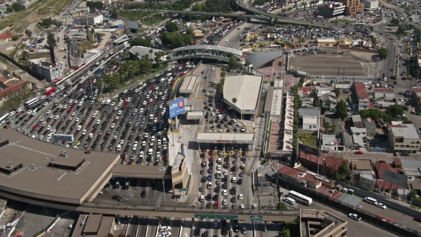 4K aerial video track traffic on the freeway to reveal the US/Mexico Border, San Ysidro Aerial Stock Footage | DCA08_056
