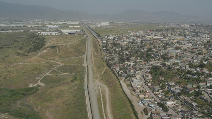 4K aerial video of following the border fences past urban neighborhoods, US/Mexico Border, Tijuana Aerial Stock Footage | DCA08_065