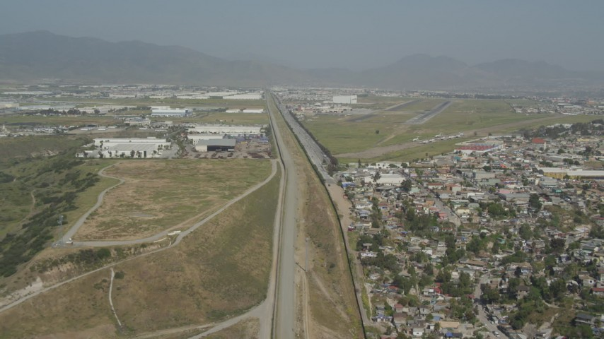 4K aerial video pass urban homes to approach warehouses and Tijuana International Airport, US/Mexico Border, Tijuana Aerial Stock Footage | DCA08_066
