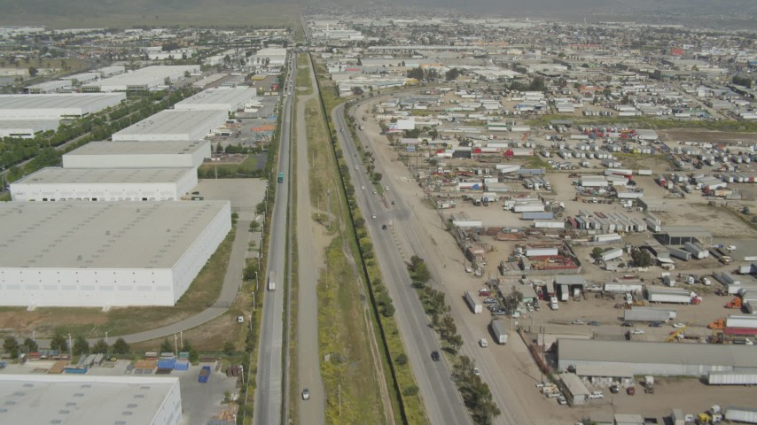 4K stock footage aerial video of flying over border fence past warehouses, US/Mexico Border, Tijuana Aerial Stock Footage | DCA08_070
