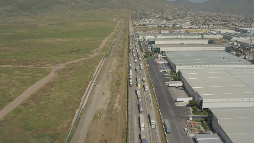 4K stock footage aerial video fly over warehouses and trucks by border fence, US/Mexico Border, Tijuana Aerial Stock Footage | DCA08_073