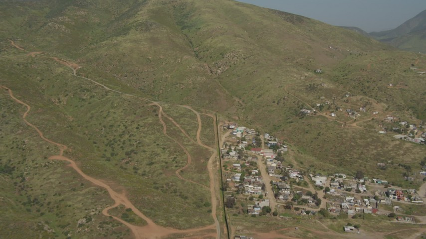 4K aerial stock footage video follow the border fence toward a mountain, US/Mexico Border, Tijuana Aerial Stock Footage | DCA08_075
