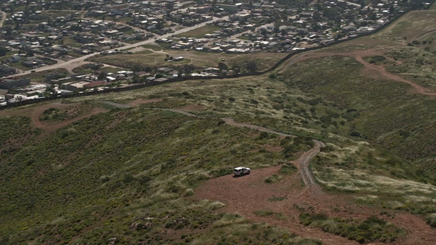 4K stock footage aerial video orbit Border Patrol and tilt to reveal Tijuana homes, US/Mexico Border, Tijuana Aerial Stock Footage DCA08_076